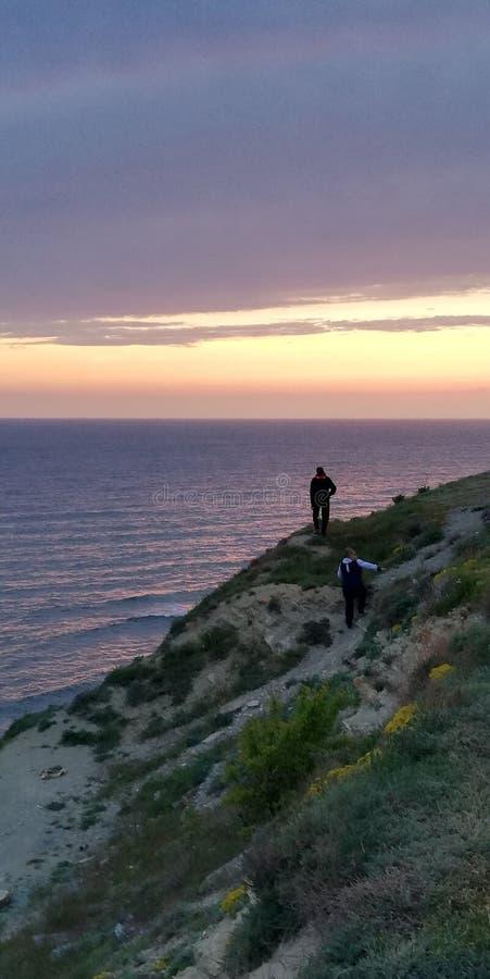 Mensen op de rots tegen het zonsondergang overzeese landschap Het overzees en de hemel zijn geschilderd in roze en purpere kleure stock afbeelding