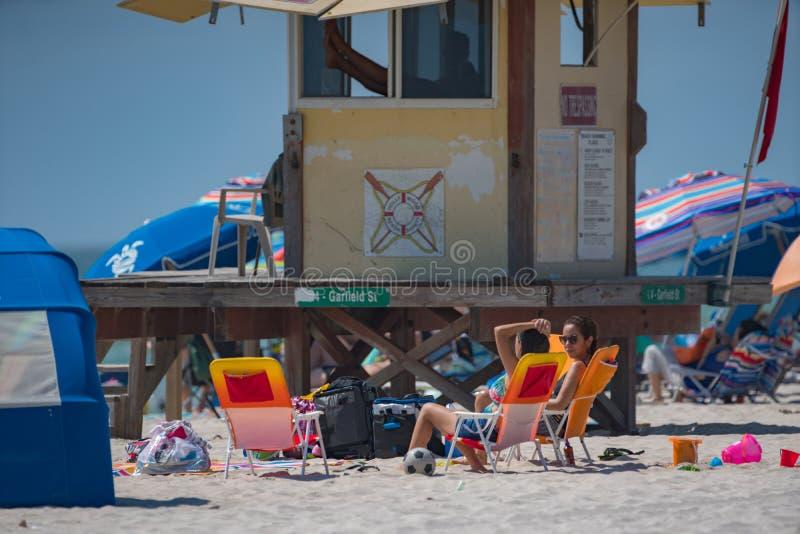 Mensen op de strandzitting dichtbij badmeestertoren stock afbeelding