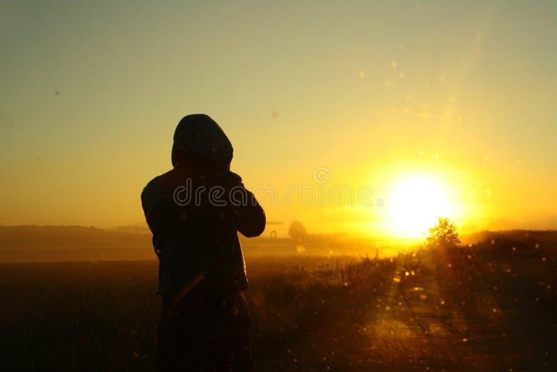 Mensen op de weg die op de zonsopgang letten De zomer stock afbeelding