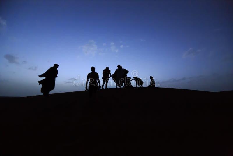 Mensen op duinen van Marokkaanse woestijn stock fotografie
