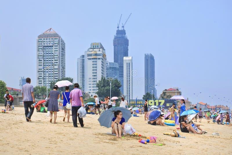 Mensen op een strand met wolkenkrabbers op de achtergrond, Yantai, China stock afbeeldingen