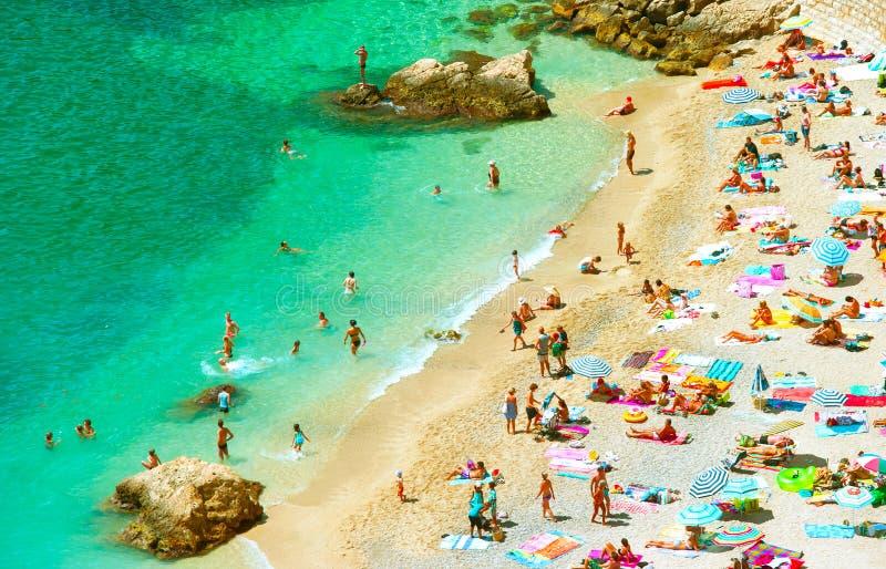 Mensen op het zandstrand De vakantieconcept van de zomer stock foto
