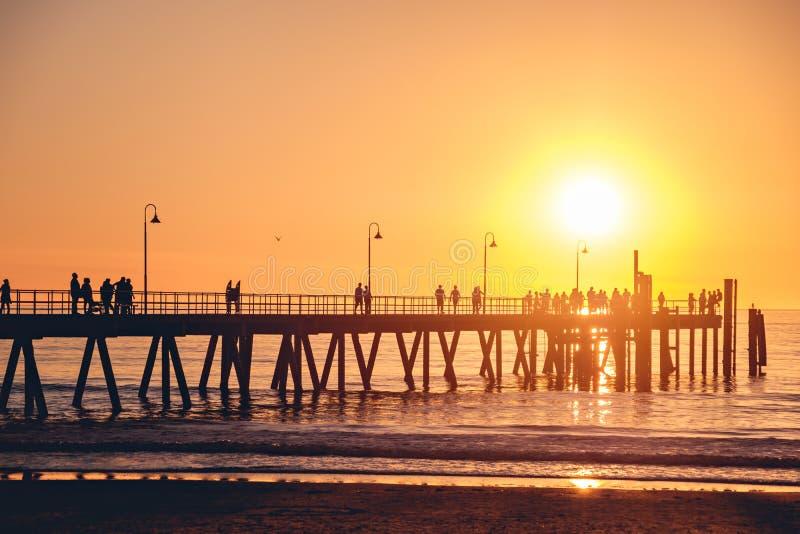 Mensen op pijler bij zonsondergang stock afbeelding