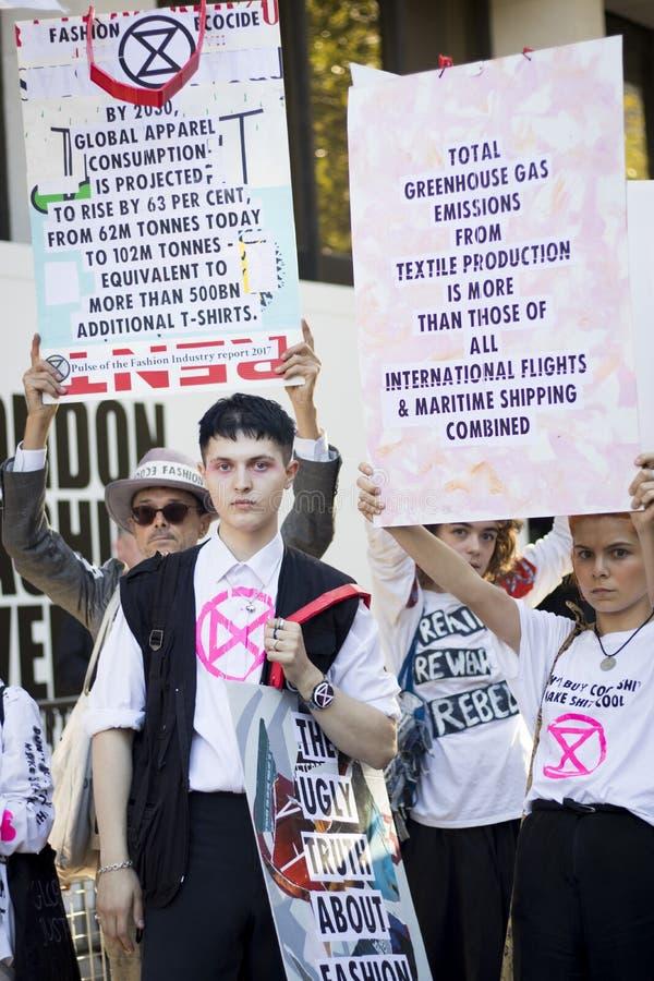 Mensen op straat tijdens de London Fashion Week Activisten protesteren tegen de modesector stock afbeelding