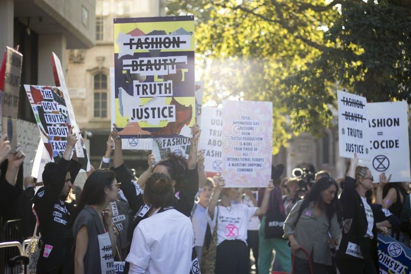 Mensen op straat tijdens de London Fashion Week Activisten protesteren tegen de modesector royalty-vrije stock afbeeldingen