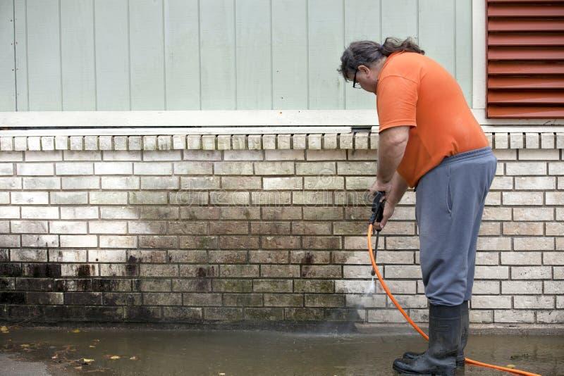 Mensen powerwashing vorm van muur - DIY stock foto's