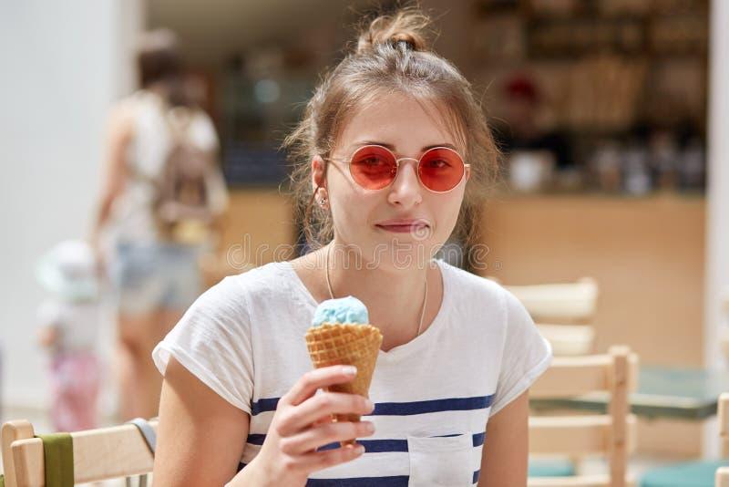 Mensen, rust, de zomer, vrije tijdsconcept Het vrij gelukkige jonge wijfje in rode zonnebril, gekleed in toevallige t-shirt, eet  stock foto