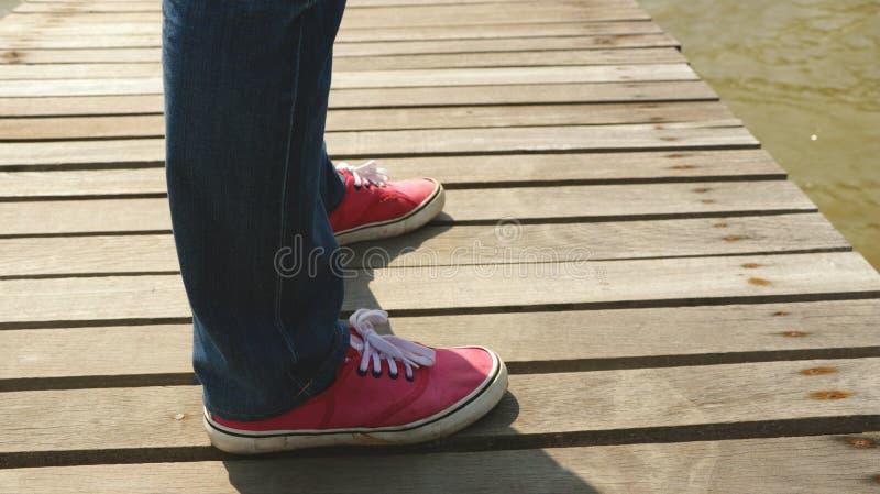 Mensen` s Benen die Jeans en Rode Stoffenschoenen op Houten Dok dragen die - zich in de Zon bevinden royalty-vrije stock afbeeldingen