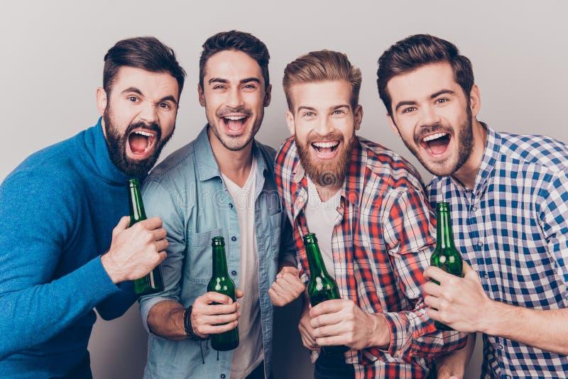 Mensen` s club Vier gekke vriendenkerels gillen met flessen i royalty-vrije stock foto
