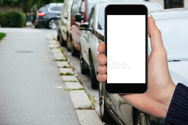 Mensen` s hand met een smartphone op de achtergrond van auto's op een stadsstraat die worden geparkeerd stock fotografie