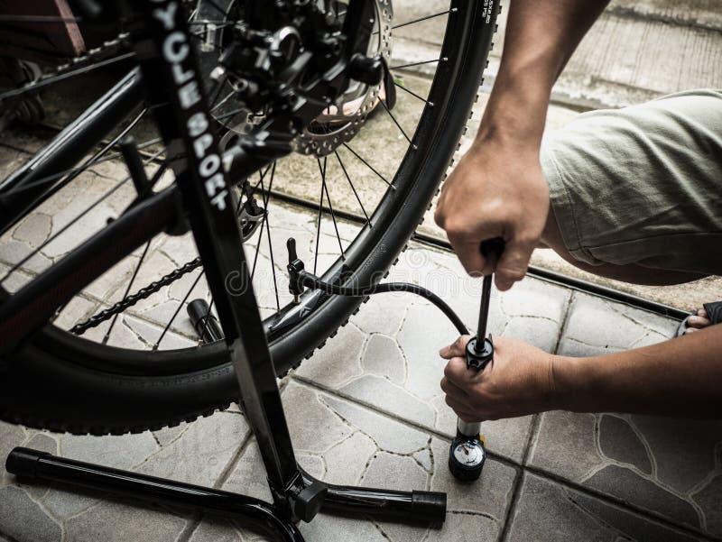 Mensen` s handen die omhoog een fietsband pompen royalty-vrije stock foto
