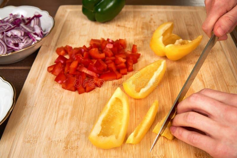 Mensen` s handen die paprika in de keuken snijden, die een maaltijd voor lunch voorbereiden royalty-vrije stock afbeelding
