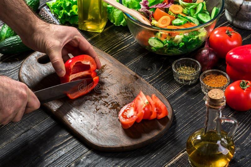 Mensen` s handen die rode paprika met mes snijden De kok sneed rode paprika De mens houdt van kokend verse salade voor diner Papr stock foto