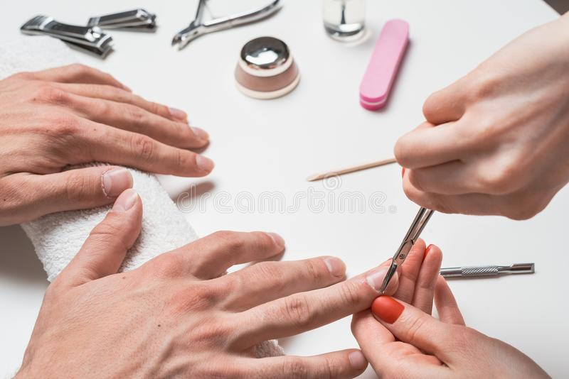mensen` s manicure de handen van de spijkertechnici snijden de spijkers van mensen` s handen stock foto