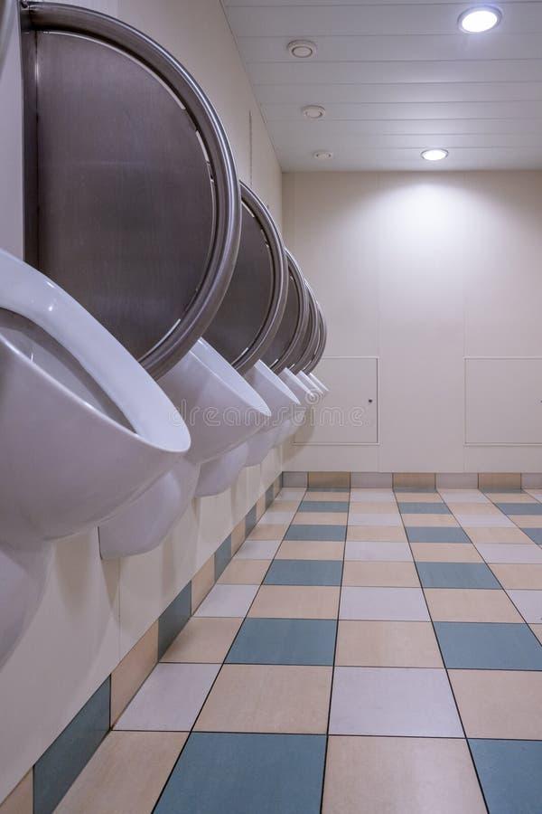 Mensen` s openbaar toilet met urinoirs op de muur en de geruite vloer stock foto