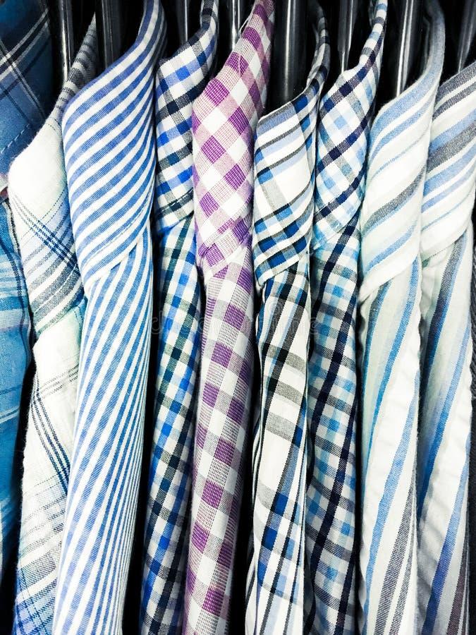 Mensen` s overhemden het hangen stock afbeelding