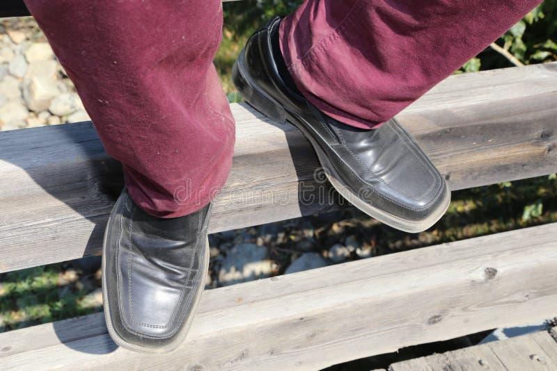 Mensen` s voeten in stoffige zwarte leerschoenen die op een stuk van hout rusten royalty-vrije stock afbeelding