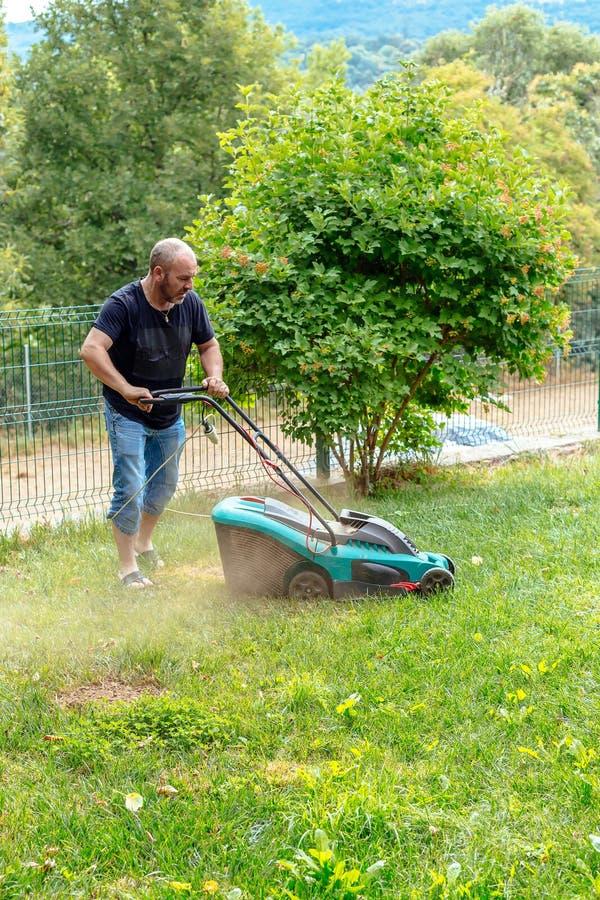 Mensen scherp gras in zijn tuin royalty-vrije stock afbeelding