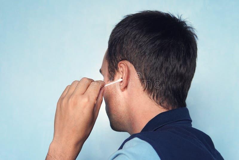Mensen schoonmakend oor met katoenen knop op blauwe achtergrond stock foto's