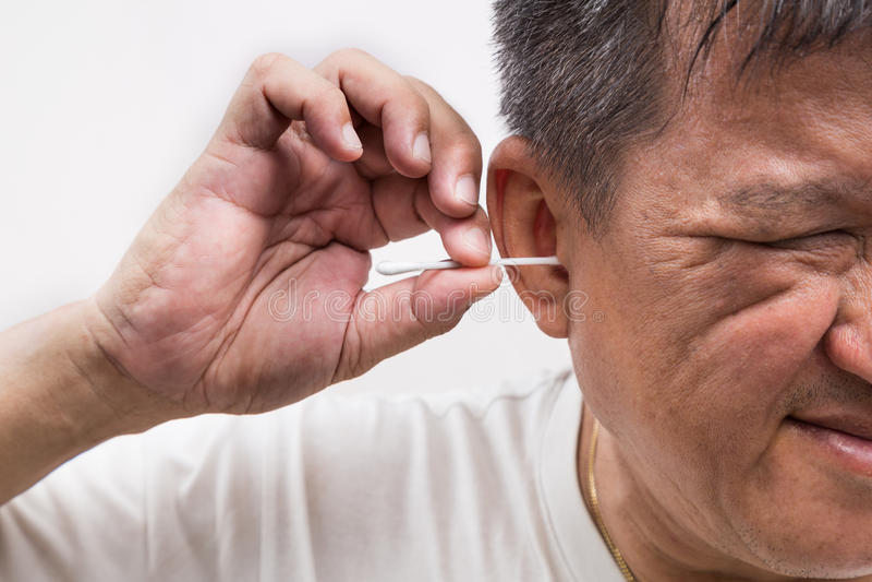 Mensen schoonmakend oor met katoenen knoppenstok met netelige uitdrukking royalty-vrije stock afbeelding