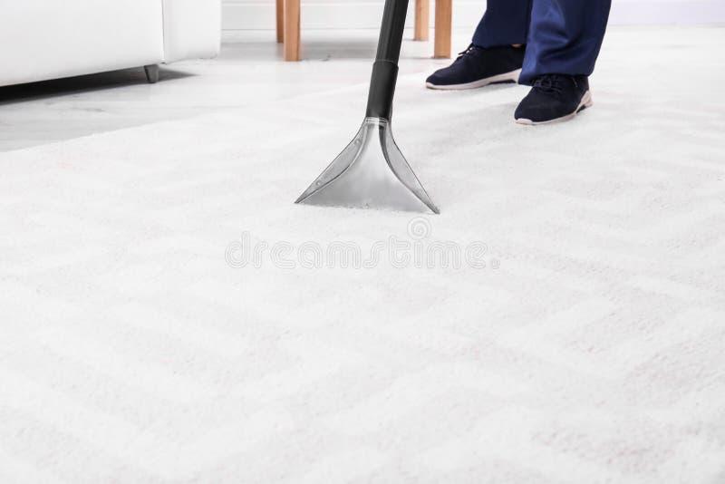 Mensen schoonmakend tapijt met stofzuiger, close-up stock fotografie