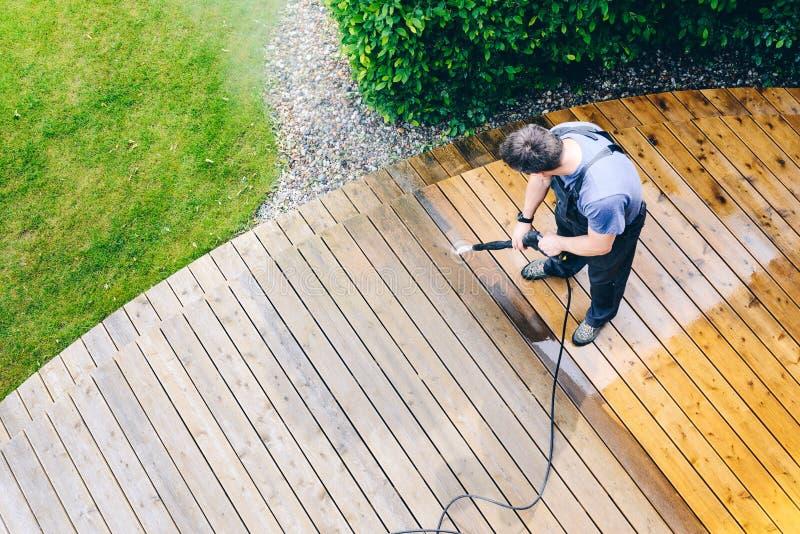 mensen schoonmakend terras met een machtswasmachine - hoogwaterdruk c stock fotografie