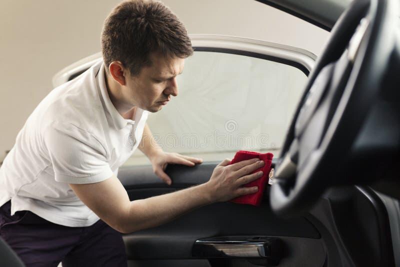 Mensen schoonmakende auto met microfiberdoek stock foto