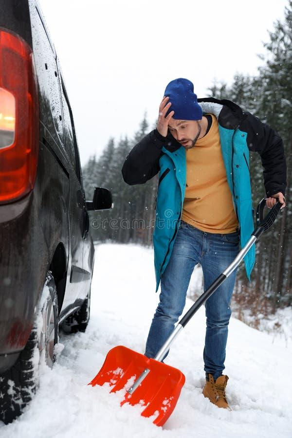 Mensen schoonmakende sneeuw met schop dichtbij geplakte auto stock fotografie