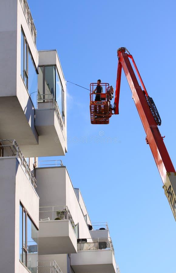 Mensen schoonmakende voorgevel van een modern minimalistic flatgebouw op een telescopische boomlift die blauwe de hemelbackgro ge royalty-vrije stock fotografie