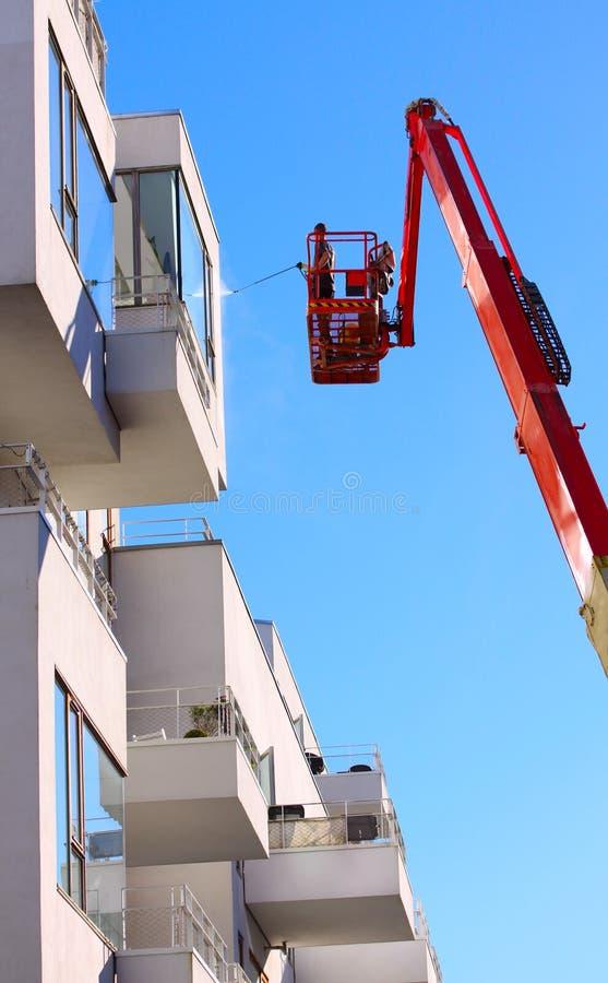 Mensen schoonmakende voorgevel van een modern minimalistic flatgebouw op een telescopische boomlift die druk straalwas met blauwe royalty-vrije stock foto's
