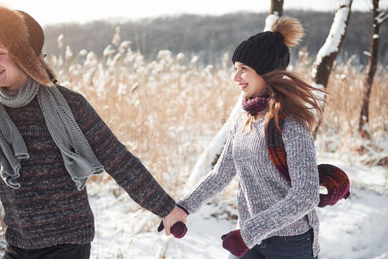 Mensen, seizoen, liefde en vrije tijdsconcept - gelukkig paar die pret over de winterachtergrond hebben royalty-vrije stock foto