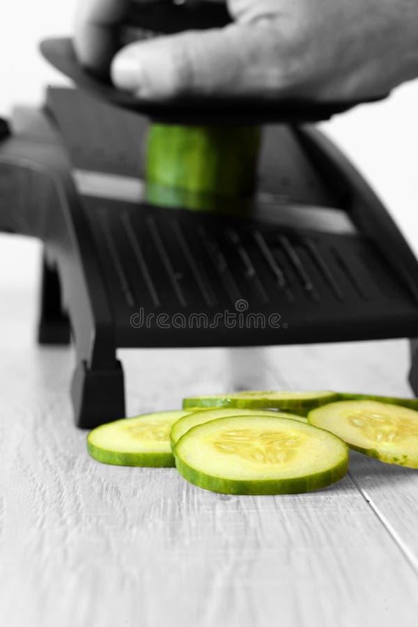 Mensen snijdende komkommer met een mandoline op een grijze houten keuken worktop stock afbeeldingen