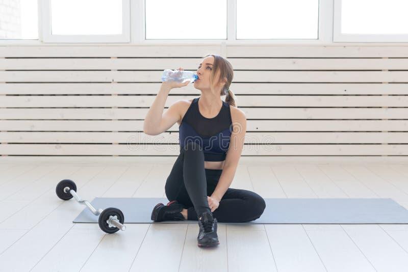 Mensen, sport en fitness concept - jonge vrouwenzitting met fles water op gymnastiekmat stock foto