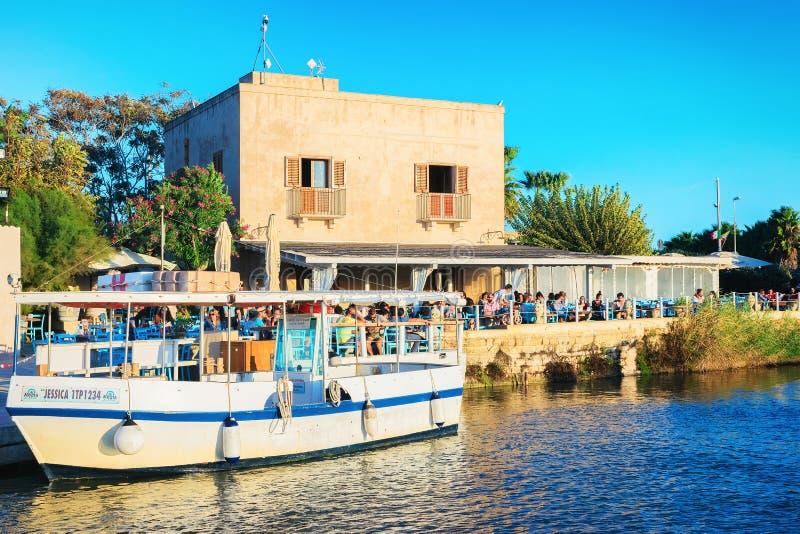 Mensen in straatkoffie bij de zoute Marsala Sicilië van de verdampingsvijver stock afbeelding