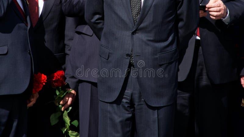 Mensen in strikte zwarte kostuums met rode bloemen Bedrijfbeheer De officiële delegatie stock foto's