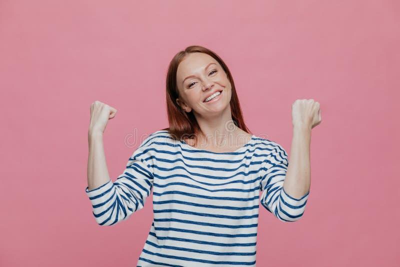 Mensen, succes, voltooiings en bepalingsconcept De gelukkige extatische mooie vrouw heft indient vuisten, viert haar overwinning  stock foto's