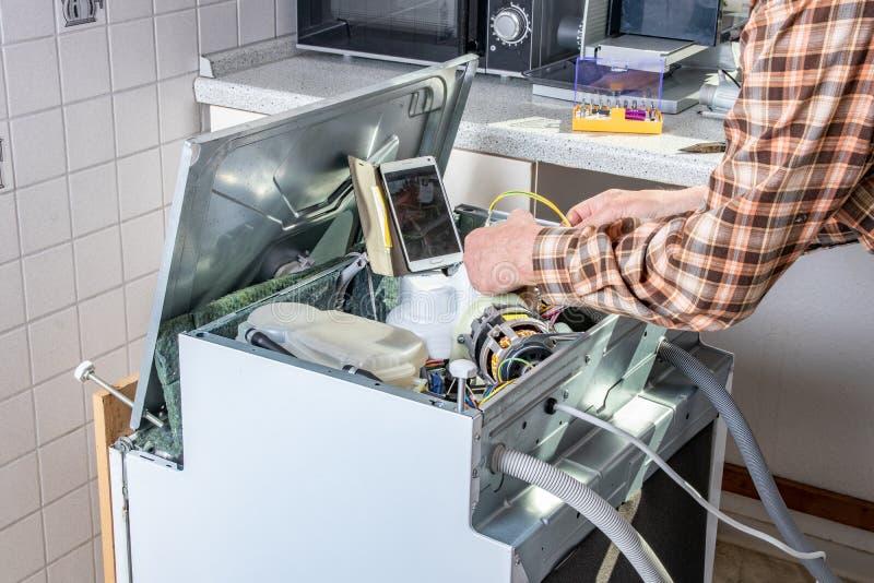 Mensen in technicusbanen De technicus of het manusje van alles de werken van de toestellenreparatie aangaande gebroken afwasmachi stock afbeeldingen