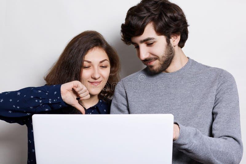 Mensen, technologie en communicatie concept Modieuze gebaarde kerel en zijn meisje online gebruikend laptop en doorbladerend Inte stock afbeeldingen