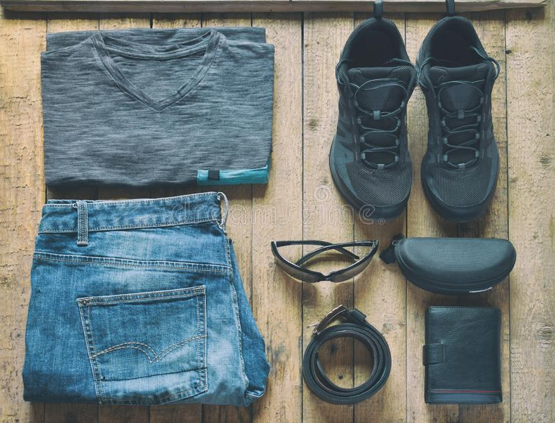 Mensen toevallige uitrustingen Mensenschoenen, kleding en toebehoren op houten achtergrond - grijze t-shirt, jeans, tennisschoene stock fotografie