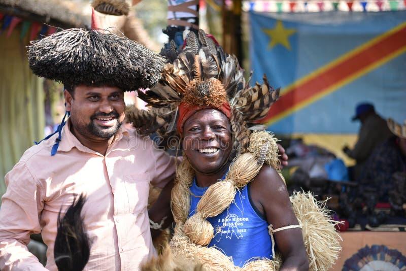 Mensen in traditionele Afrikaanse Stammenkleding, die van de markt genieten