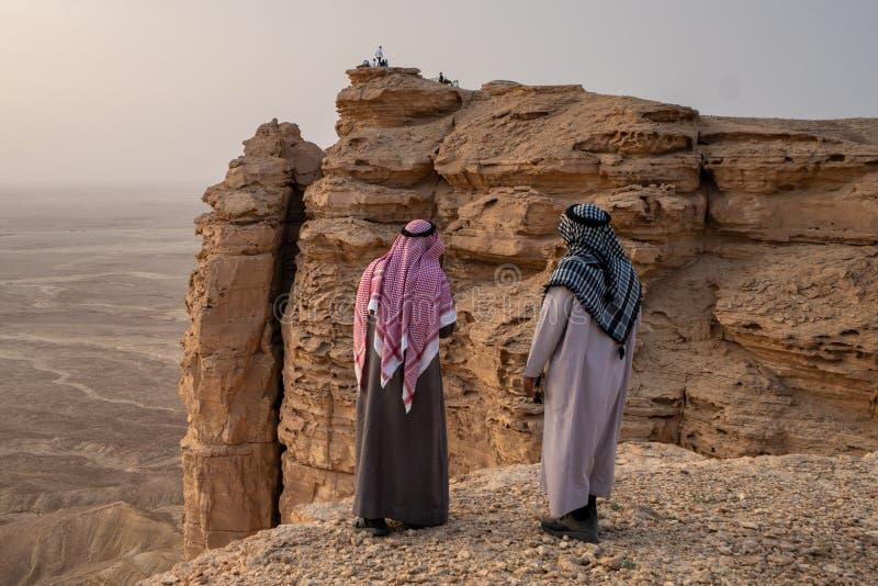 2 mensen in traditionele kleding bij de Rand van de Wereld dichtbij Riyadh in Saudi-Arabië stock afbeelding