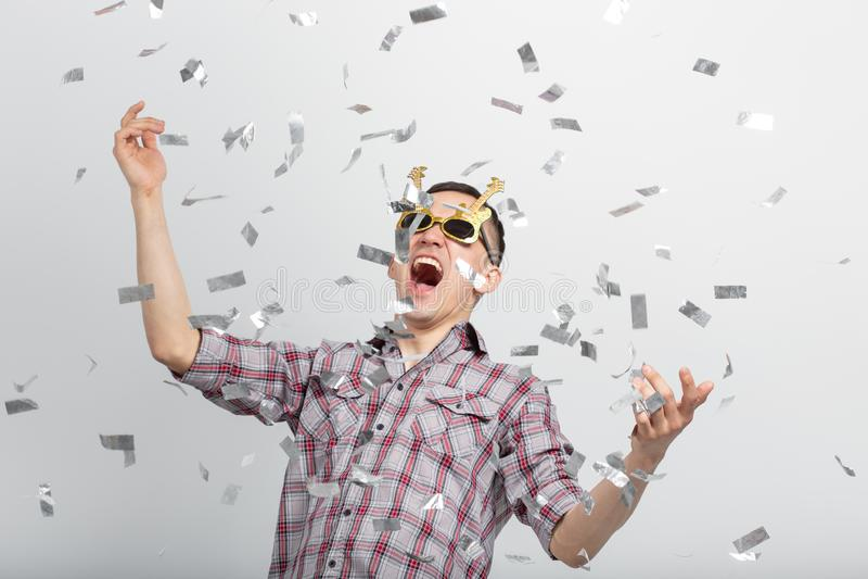 Mensen, vakantie en partijconcept - grappige kerel in glazen die in confettien op witte achtergrond dansen royalty-vrije stock foto's