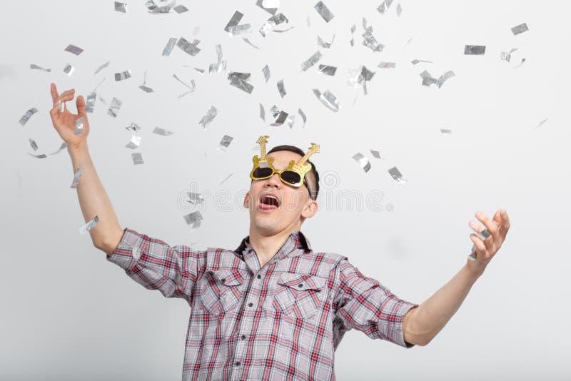 Mensen, vakantie en partijconcept - grappige kerel in glazen die in confettien op witte achtergrond dansen stock fotografie