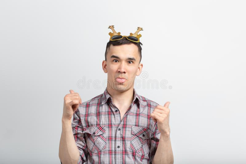 Mensen, vakantie en partijconcept - grappige kerel met glazen die duimen in confettien op witte achtergrond tonen stock afbeeldingen