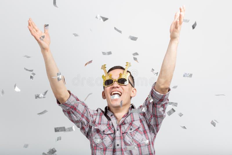 Mensen, vakantie en partijconcept - Koele mens in plaidoverhemd over witte achtergrond met confettien stock foto