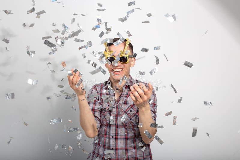 Mensen, vakantie en partijconcept - Mens met grappig gezicht in plaidoverhemd met confettien royalty-vrije stock foto's