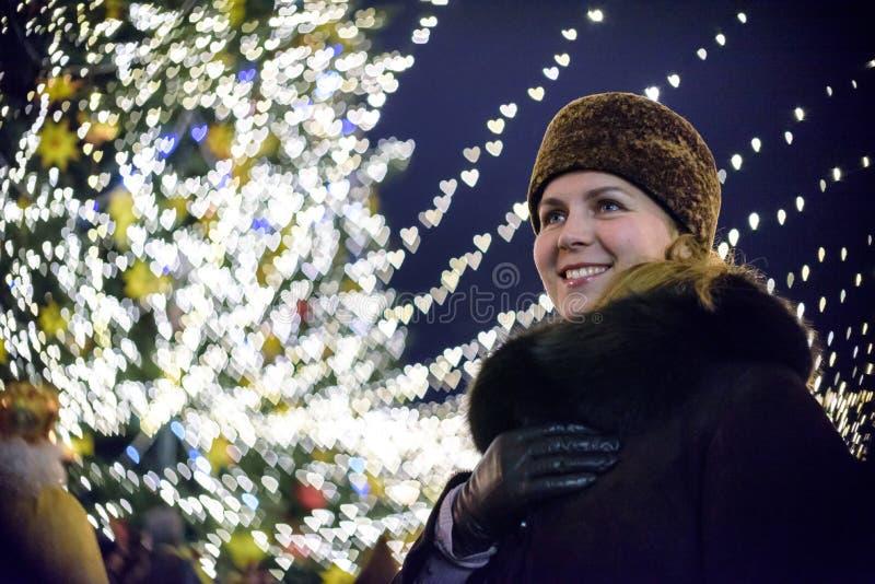 Mensen, vakantie, Kerstmis en magisch concept - lachende vrouw in avondjurkholding iets over de sneeuwachtergrond van de nachtsta royalty-vrije stock afbeeldingen