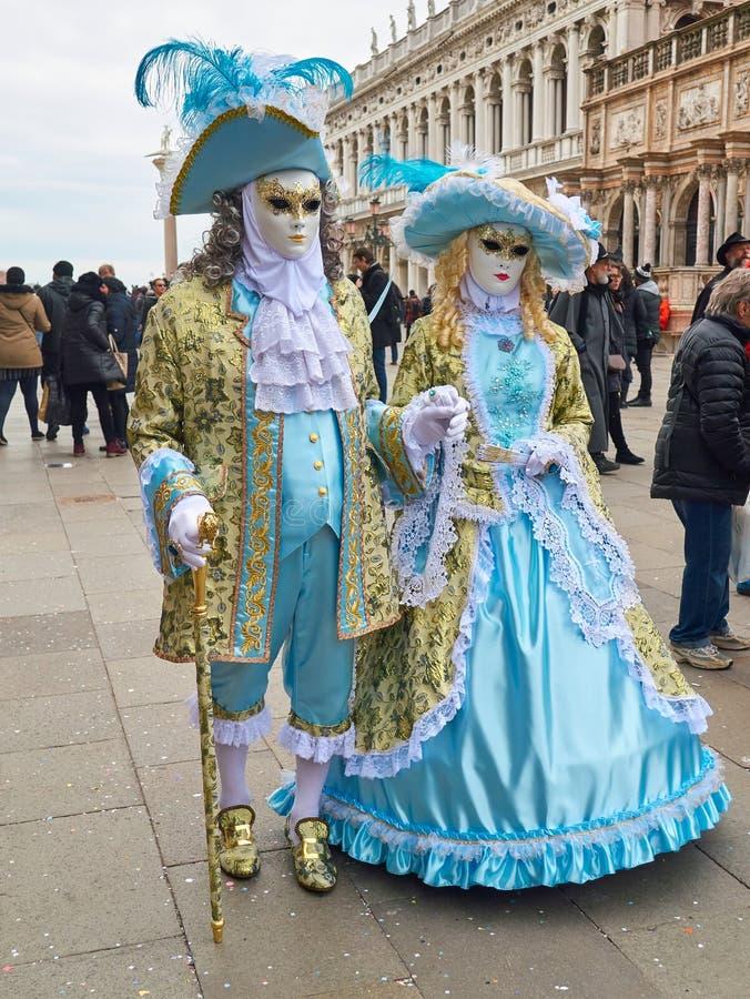 Mensen in Venetiaanse maskers bij St Teken` s Vierkant in Venetië, Italië stock afbeelding