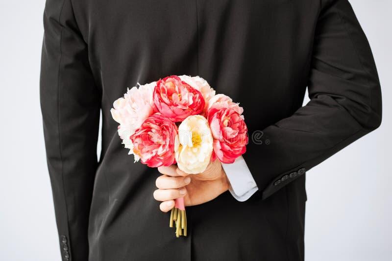Mensen verbergend boeket van bloemen stock fotografie