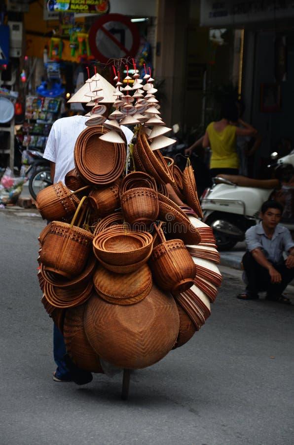 Mensen verkopende hoeden en manden op een fiets in de stad van Hanoi stock afbeeldingen